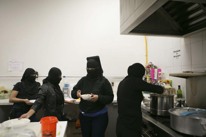 Women's rights activists who say they cover their faces because they fear for their safety, serve dinner in the kitchen at the offices of the Mexican Human Rights Commission (CNDH), which they have been occupying for almost three months in Mexico City, Monday, Nov. 16, 2020. Feminist activists are occupying the CNDH to demand justice for the victims of sexual abuse, femicide, and other gender violence, and have opened it as a refuge to victims of sexual violence, where some mothers have brought their children to live while the government either failed to solve or even investigate the rapes of their daughters. (AP Photo/Ginnette Riquelme)