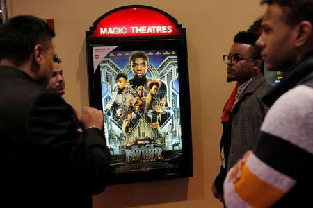 """A group of men gather in front of a poster advertising the film """"Black Panther"""" on its opening night of screenings at the AMC Magic Johnson Harlem 9 cinemas in Manhattan, New York, U.S., February 15, 2018. REUTERS/Andrew Kelly"""