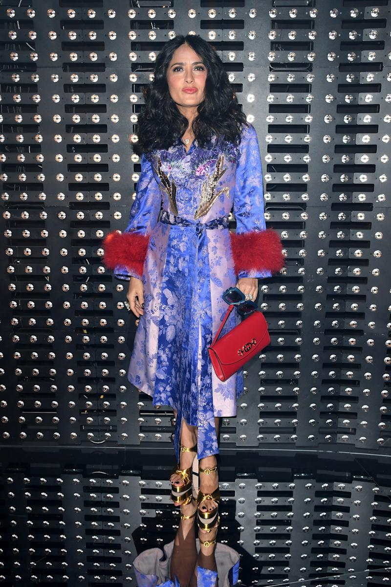 Salma Hayek looks dazzling in purple overall dress and matches it with a gold heel sandals.
