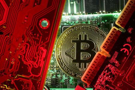 FILE PHOTO: Copy of bitcoin standing on PC motherboard is seen in this illustration picture