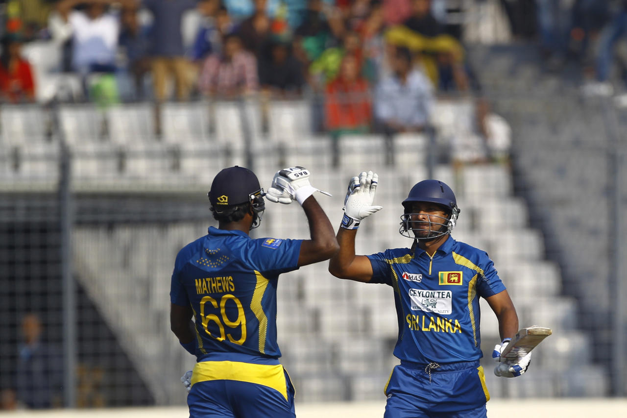 Sri Lanka's Kumar Sangakkara, right, celebrates with his teammate Angelo Mathews after scoring a century during the second one day international (ODI) cricket match against Bangladesh in Dhaka, Bangladesh, Thursday, Feb. 20, 2014. (AP Photo/A.M. Ahad)