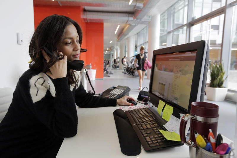 Zayna Abdul, 34, an Abigail Michaels concierge, works at her desk in the the Mercedes House apartments, in New York,  Monday, March 25, 2013. A brownstone overlooking Central Park is no longer enough for the well-to-do New Yorker on the hunt for an apartment. What the very wealthy want now is the ease of hotel living in their own apartment buildings. That means room service delivered from the restaurant down the street, a concierge who will handle even the most outlandish requests and, of course, a spa in the lobby. There is no amenity left behind in Manhattan's soaring luxury real estate market.(AP Photo/Richard Drew)