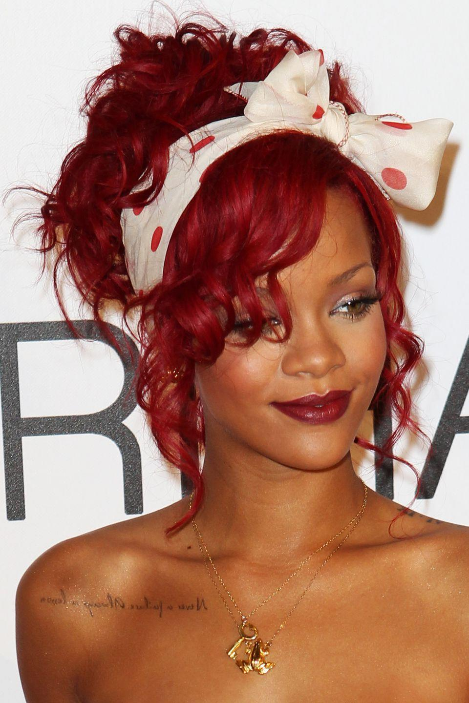 <p>Rihanna wears her cherry-red hair curly and in an updo. We love the addition of the coordinating scarf tied into a neat bow. </p>