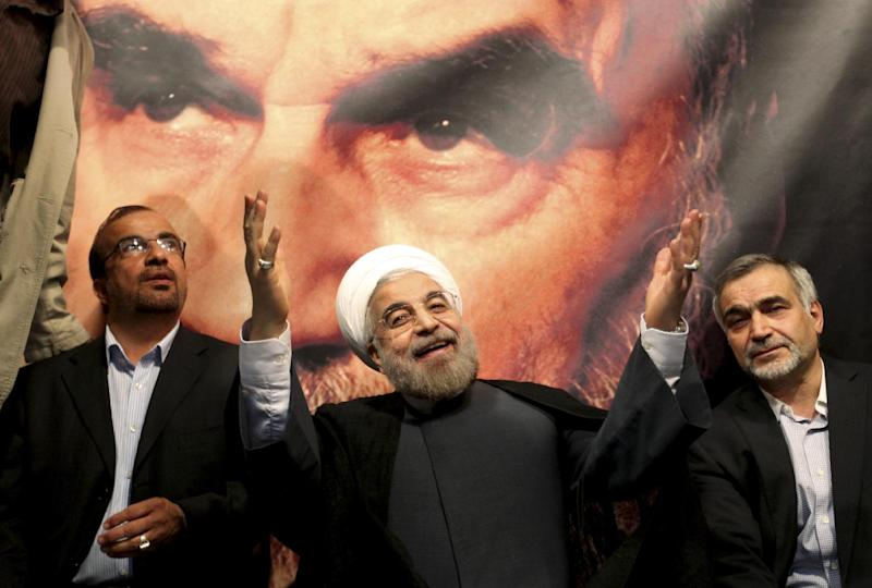 FILE -- In front of a portrait of the late Iranian revolutionary founder Ayatollah Khomeini, presidential candidate Hasan Rowhani, a former top nuclear negotiator, center, gestures to his supporters at a rally in Tehran, Iran, Saturday, June 1, 2013. Iran's reformist-backed presidential candidate surged to a wide lead in early vote counting Saturday, June 15, 2013, a top official said, suggesting a flurry of late support could have swayed a race that once appeared solidly in the hands of Tehran's ruling clerics. (AP Photo/Ebrahim Noroozi, File)