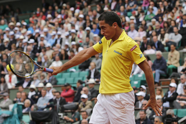 Nicolas Almagro of Spain returns in his quarter final match against compatriot Rafael Nadal at the French Open tennis tournament in Roland Garros stadium in Paris, Wednesday June 6, 2012. (AP Photo/Christophe Ena)