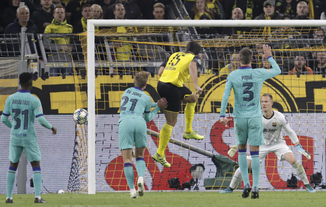 Dortmund's Mats Hummels, center, heads the ball wide during the Champions League Group F soccer match between Borussia Dortmund and FC Barcelona in Dortmund, Germany, Tuesday, Sept. 17, 2019. (AP Photo/Michael Probst)