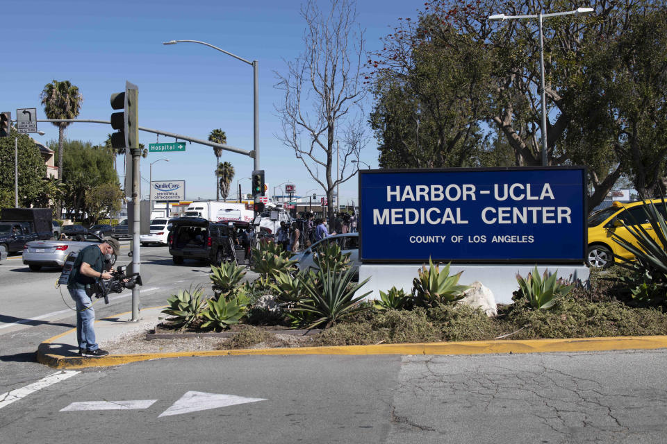 Members of the media gather outside an entrance to Harbor-UCLA Medical Center, Tuesday, Feb. 23, 2021, in Torrance, Calif., where golfer Tiger Woods was hospitalized there following a car accident. (AP Photo/Kyusung Gong)