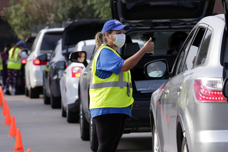 Lisa Iparrea, director of client services, gives a thumbs up as she helps direct cars through the touchless drive thru food distribution line at the West Houston Assistance Ministries Wednesday, Oct. 14, 2020, in Houston. Many people in Houston and around the U.S. live paycheck to paycheck and were caught off guard by the economic fallout from the coronavirus that initially cost the nation 22 million jobs, with 10.7 million still unemployed. (AP Photo/Michael Wyke)