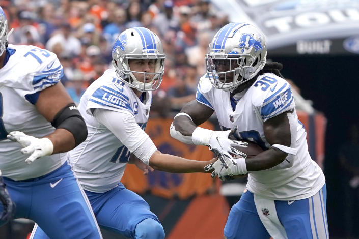 Detroit Lions quarterback Jared Goff, left, hands off to running back Jamaal Williams during the first half of an NFL football game against the Chicago Bears Sunday, Oct. 3, 2021, in Chicago. (AP Photo/David Banks)