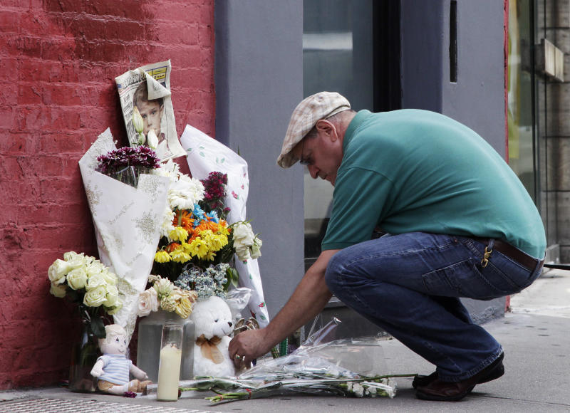 David Lutzker places a Snoopy figurine at a makeshift memorial next to a building where Etan Patz was reportedly killed 33 years ago in the SoHo neighborhood of New York, Monday, May 28, 2012. For prosecutors, the work is just beginning after the astonishing arrest last week of a man who police say confessed to strangling a 6-year-old New York City boy three decades earlier in one of the nation's most bewildering missing children's cases. Pedro Hernandez, 51, was charged with second-degree murder in the 1979 death of Etan Patz, based largely on a signed confession he gave to detectives. (AP Photo/Mark Lennihan)