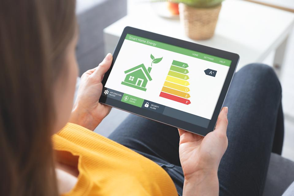 A woman looking at an energy efficiency app on a tablet screen
