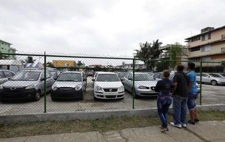 People look at used cars for sale at the government owned dealership in Havana