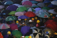 Pro-democracy protesters wear raincoats stand under umbrella during rainfall at an anti-government protest at Victory Monument during a protest in Bangkok, Thailand, Sunday, Oct. 18, 2020. Thai police on Sunday declined to say whether they were taking a softer approach toward student anti-government demonstrations, after several mass rallies attracting thousands of protesters ended peacefully in Bangkok on Saturday. (AP Photo/Sakchai Lalit)