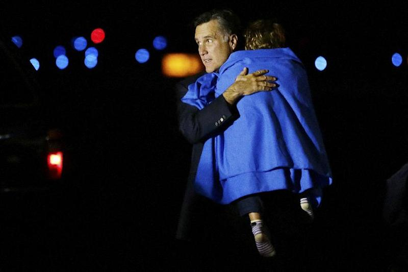 Republican presidential candidate and former Massachusetts Gov. Mitt Romney carries one of his grandsons as he steps off his campaign plane at Pease International Airport in Portsmouth, N.H., early Saturday, Nov. 3, 2012, as they arrive from Cincinnati, Ohio. (AP Photo/Charles Dharapak)