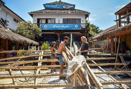 Foreigners clean up the damaged parts of their restaurant after Sunday's earthquake on Gili Trawangan island, North Lombok, Indonesia August 8, 2018 in this photo taken by Antara Foto. Antara Foto/Ahmad Subaidi/ via REUTERS