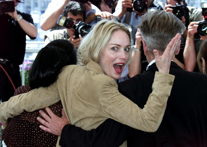 U.S. actress Sharon Stone (C) looks back at photographers as she stands next to U.S. director David Lynch (R), President of the Jury at the 55th International Cannes Film Festival, and Indonesian actress Christine Hakim (L), during a photo call in Cannes May 15, 2002. REUTERS/Jean Paul Pelissier VK
