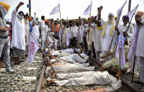 Farmers shout slogans as they block a railway track protesting against the new farm bills, at Devi Dass Pura village, about 20 kilometers from Amritsar, India, Thursday, Sept. 24, 2020. Farmers across the state have threatened to stop train services as they demanded a rollback in three new farm bills of the central government, stating that these are against the interests of farmers. (AP Photo/Prabhjot Gill)