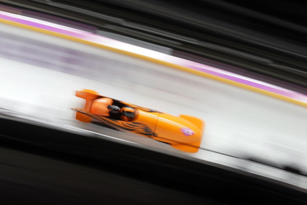 The team from the Netherlands NED-1, piloted by Edwin van Calker and brakeman Bror van der Zijde, speed down the track on their second run during the men's two-man bobsled competition at the 2014 Winter Olympics, Sunday, Feb. 16, 2014, in Krasnaya Polyana, Russia. (AP Photo/Natacha Pisarenko)