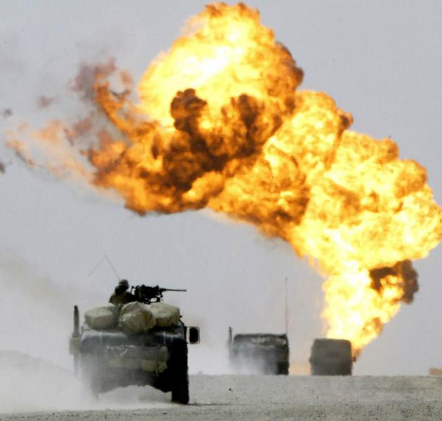 A March 22 2003 file photo shows a marines convoy from the 3rd Light Armoured Reconnaisance Battallion passes through the southern Iraqi al-Ratka oilfield heading towards Baghdad. Iraqi troops set fire to the oil field as they fled from coalition forces advancing on Baghdad. The US-led invasion of Iraq that toppled Saddam Hussein sought to enshrine a liberal democracy in the heart of the Middle East but instead unleashed brutal sectarian violence and endless political disputes.
