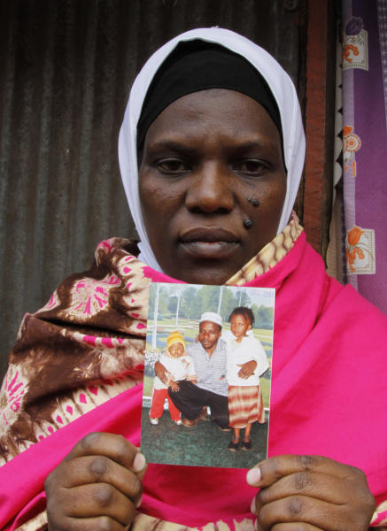 Latifah Naiman Mariki, widow of the late Haji Lukindo, holds a family photo showing her late husband and her two daughters outside her house in Nairobi, Kenya, Friday, Aug. 2, 2013. An American diplomat who police say was speeding crossed the center line in his SUV and rammed into a full mini-bus, killing a father of three whose widow is six months pregnant, officials said Friday. Latifah Naiman Mariki, 38, and whose husband was killed in the crash, was almost evicted from her house this week after her landlord demanded rent. Mariki's deceased husband, Haji Lukindo, was the family's only source of income. Mariki told The Associated Press that neither the American driver nor anyone at the U.S. Embassy has contacted her, and she doesn't know how she will provide for her soon-to-be-born child and three children, ages 20, 10 and 7. (AP Photo/Khalil Senosi)