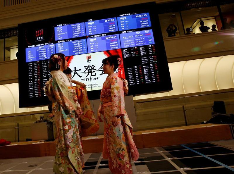 Women, dressed in ceremonial kimonos, stand in front of an electronic board showing stock prices after the New Year opening ceremony at the Tokyo Stock Exchange (TSE), held to wish for the success of Japan's stock market, in Tokyo