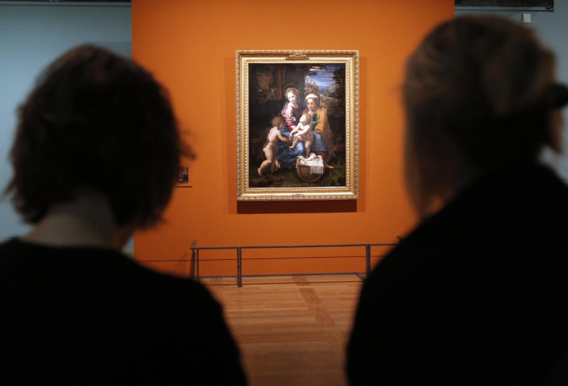 """Women watch """"Holy Family (La Perla) """", a painting by Raphael as part of the exhibition """"Late Raphael"""" at the Louvre museum, in Paris, Tuesday, Oct. 9, 2012. This exhibition, organized by the Louvre from Oct. 11 to Jan.14, 2013 in partnership with the Prado Museum, brings together the works produced by Raphael in Rome during the last years of his life. (AP Photo/Christophe Ena"""