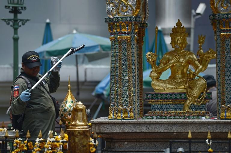A policeman inspects the cordoned-off site of a bomb blast at the popular Erawan shrine in the heart of Bangkok's tourist and commercial centre, on August 18, 2015