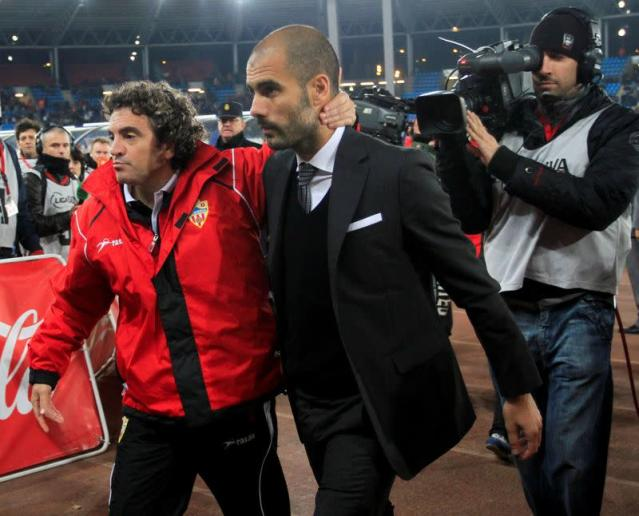 FILE PHOTO: Almeria's coach Lillo and Barcelona's coach Guardiola leave the pitch at the end of their Spanish first division soccer match against Barcelona in Almeria.