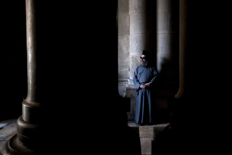 A Christian clergyman stands inside the Church of the Holy Sepulchre, traditionally believed to be the burial site of Jesus Christ, in Jerusalem's Old City, Thursday, May 30, 2013. (AP Photo/Sebastian Scheiner)