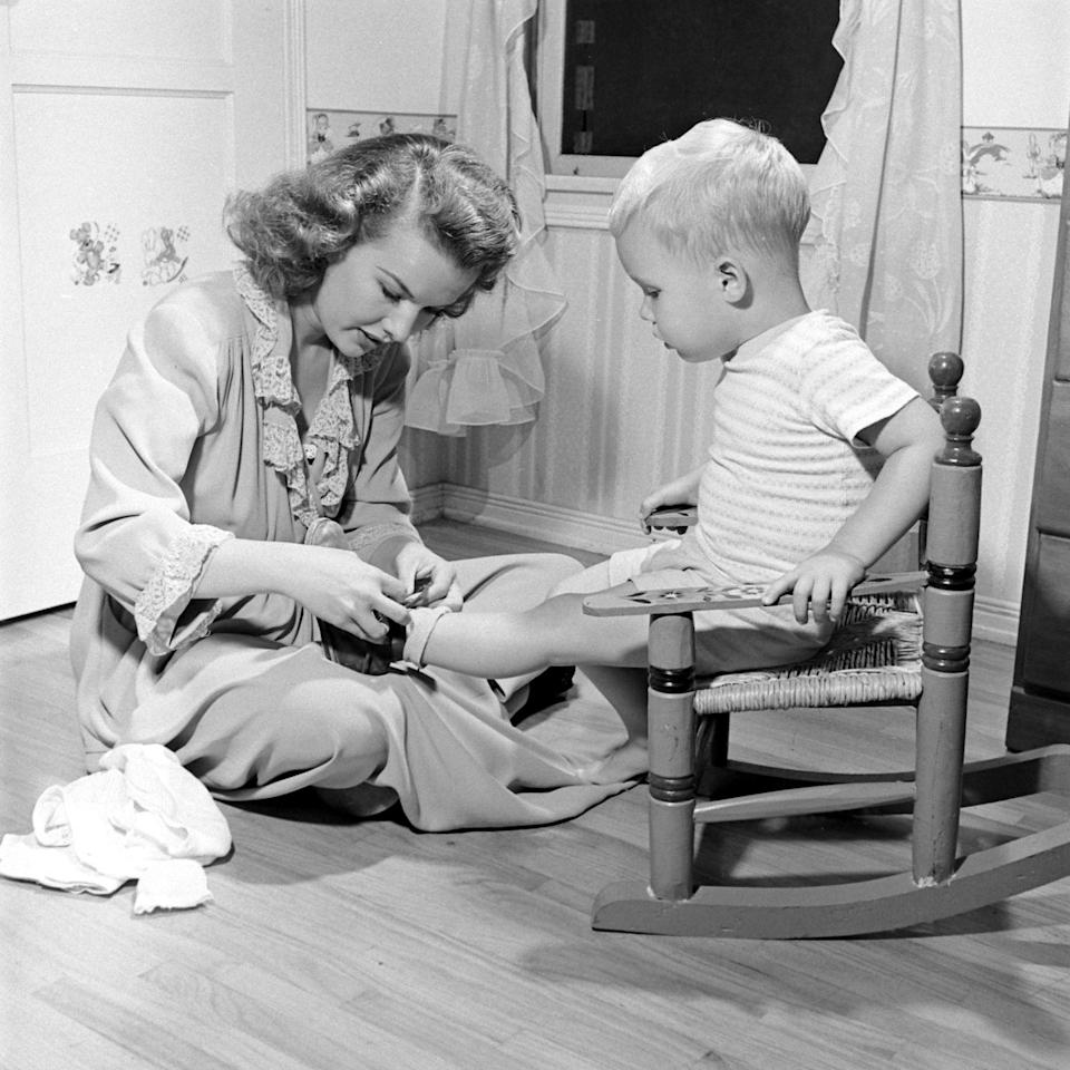 <p>The television star helps her toddler tie his shoe while at home in Los Angeles in 1945. </p>