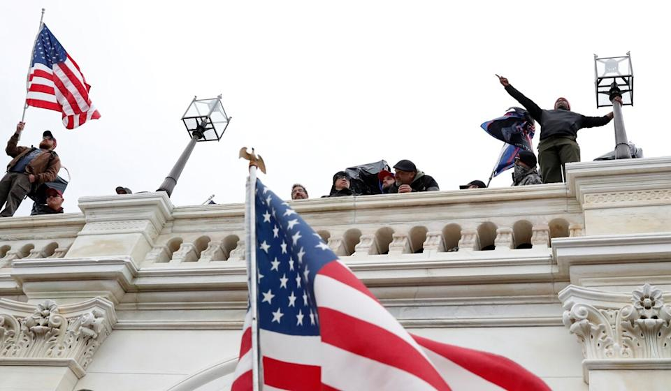 Trump supporters wave American flags after breaching the Capitol barricades to contest the congressional certification of the 2020 US presidential election results at the Capitol in Washington on Wednesday. Photo: Reuters