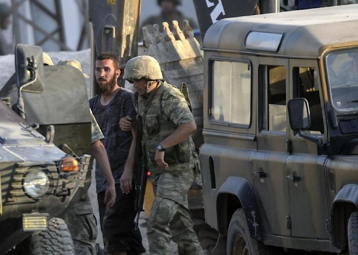 Turkish soldiers detain a man (C) who crossed over from Syria, and whom they believe to be an Islamic State (IS) fighter near the Akcakale crossing gate between Turkey and Syria at Akcakale in Sanliurfa province on June 15, 2015 (AFP Photo/Bulent Kilic)