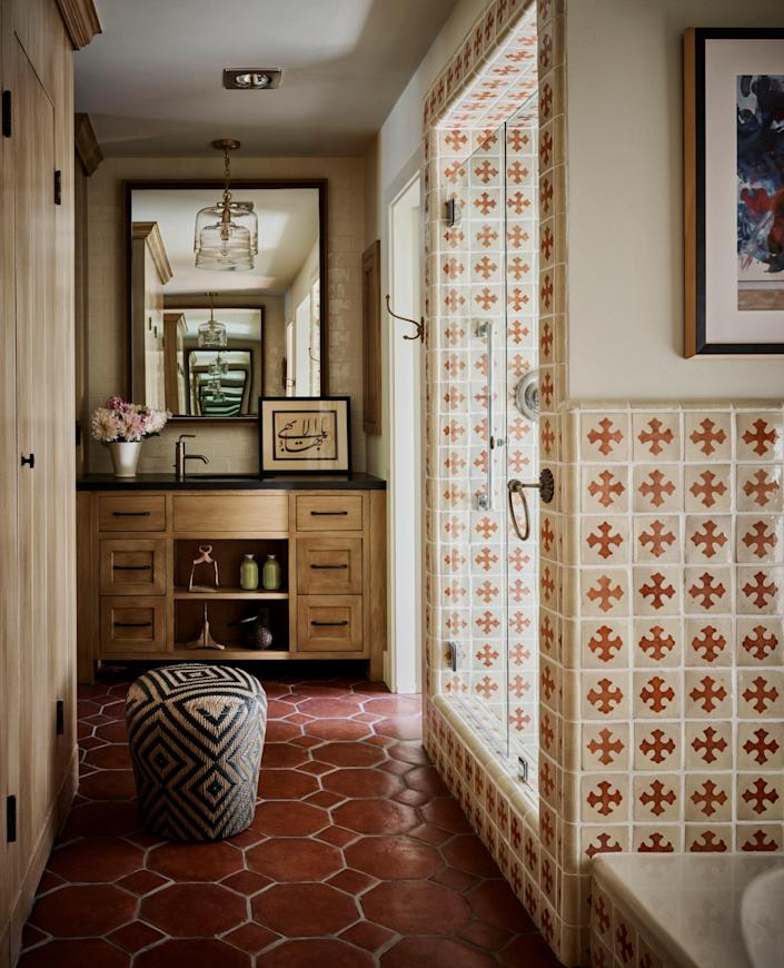 "<div class=""caption""> The main bathroom's original tiles were preserved while the vanities at both ends of the space were replaced with more user-friendly contemporary designs. </div>"
