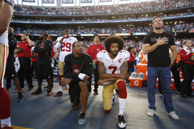 "Eric Reid, left and Colin Kaepernick of the <a class=""link rapid-noclick-resp"" href=""/nfl/teams/san-francisco/"" data-ylk=""slk:San Francisco 49ers"">San Francisco 49ers</a> kneel on the sideline during the national anthem as free agent and former Green Beret Nate Boyer, right, stands before a game against the San Diego Chargers in 2016. (Michael Zagaris/San Francisco 49ers/Getty Images)"