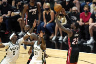 Miami Heat guard Kendrick Nunn (25) shoots over Milwaukee Bucks center Bobby Portis (9) and guard Jrue Holiday (21) during the second half of Game 4 of an NBA basketball first-round playoff series, Saturday, May 29, 2021, in Miami. (AP Photo/Lynne Sladky)