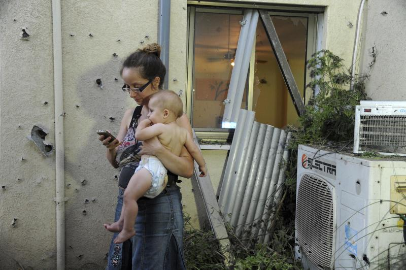An Israeli woman holds her child outside her home damaged by a rocket fired from Lebanon in Shavei Tzion outside Nahariya in northern Israel, Thursday, Aug. 22, 2013. Military spokesman Lt. Col. Peter Lerner said Thursday that three rockets landed in northern Israel, while one was shot down. (AP Photo/Jinipix) ISRAEL OUT