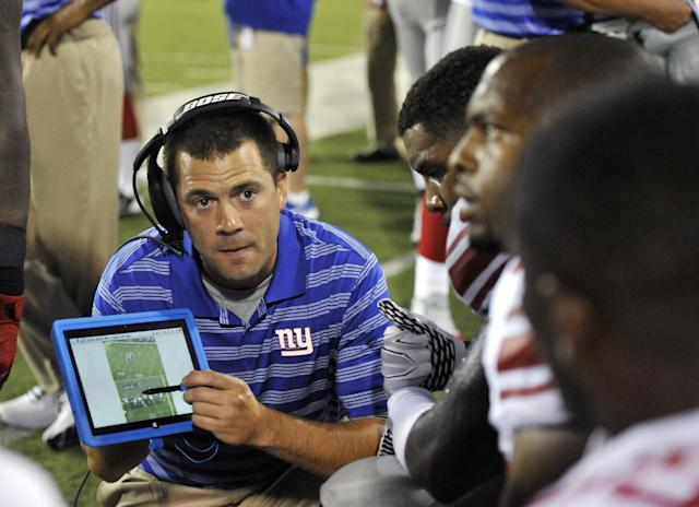 New York Giants tight ends coach Kevin Gilbride uses a Microsoft Surface tablet at the Pro Football Hall of Fame exhibition NFL football game against the Buffalo Bills Sunday, Aug. 3, 2014, in Canton, Ohio. (AP Photo/David Richard)