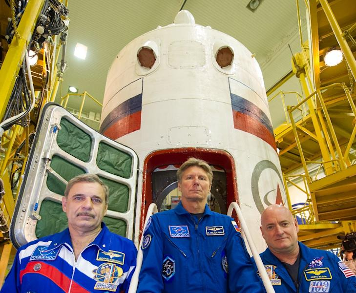 (From left) Russian cosmonauts Mikhail Kornienko and Gennady Padalka and US astronaut Scott Kelly pose in front of the Soyuz TMA-16M space vehicle at an assembling department at the Russian leased Baikonur cosmodrome on March 23, 2015. (AFP Photo/Stringer)
