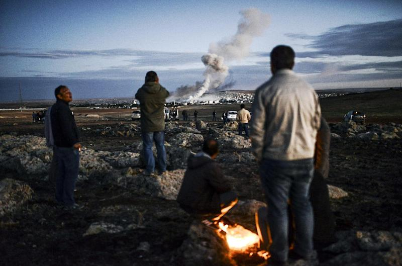 Kurdish people observe smoke rising from the Syrian town of Kobane, also known as Ain al-Arab, following an explosion as seen from the southeastern Turkish village of Mursitpinar in the Sanliurfa province on October 20, 2014 (AFP Photo/Bulent Kilic)