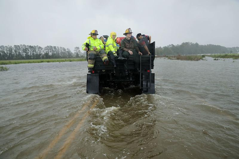 Rescue workers from Township No. 7 Fire Department and volunteers from the Civilian Crisis Response Team use a truck to move people rescued from their flooded homes during Hurricane Florence in James City on Friday.