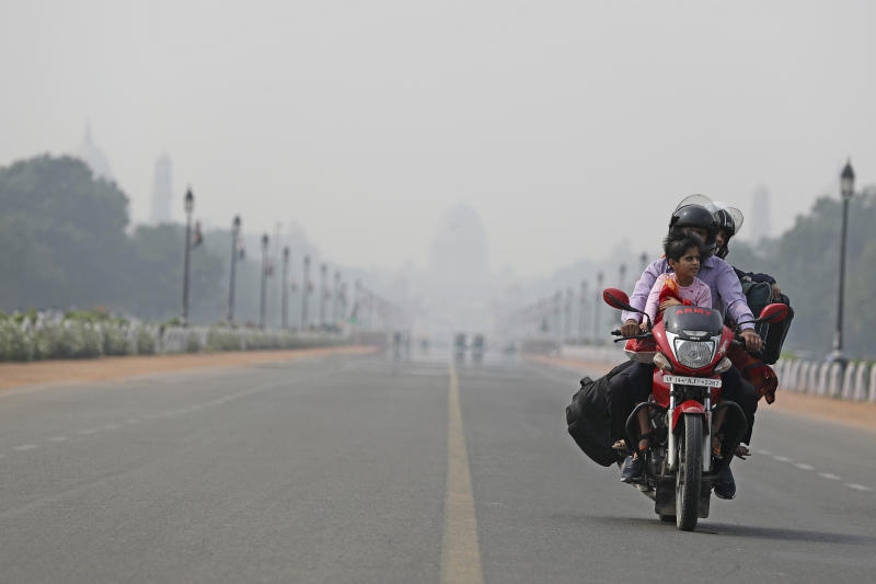 India's Presidential Palace, in the backdrop, is covered with smog as a family rides a motorbike on Rajpath, the ceremonial boulevard, in New Delhi, India, Tuesday, Nov. 19, 2019. India's Parliament has discussed the toxic air threatening the lives of the capital region's 48 million people, with opposition leaders demanding the creation of a parliamentary panel to remedy the situation on a long-term basis. (AP Photo/Altaf Qadri)