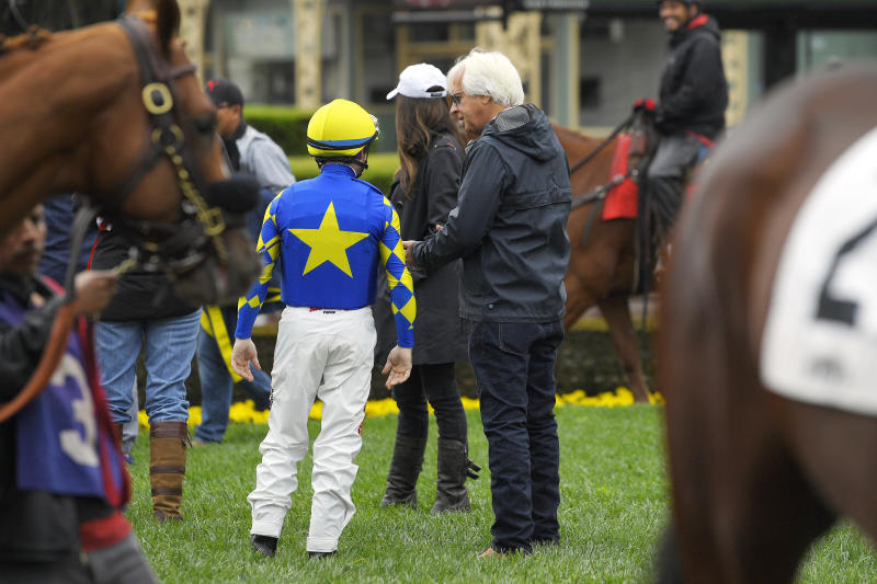 Jockey Drayden Van Dyke, left, talks with trainer Bob Baffert before riding Charlatan in the sixth race at Santa Anita on Saturday, March 14, 2020, in Arcadia, Calif. Charlatan won the horse race. (AP Photo/Mark J. Terrill)