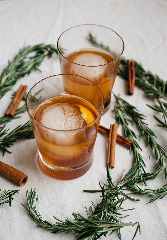 """<p>There's nothing like tapping holiday favorites for your menu—and then using them as an added decorative moment. Set up a dark wood bar stocked with amber-toned spirits and encourage guests to pop in throughout the night for a craft cocktail of their choice. We suggest serving wintery riffs on classic cocktails, like the <a href=""""https://saltedplains.com/cinnamon-rosemary-old-fashioned/"""" rel=""""nofollow noopener"""" target=""""_blank"""" data-ylk=""""slk:cinnamon rosemary old fashioned"""" class=""""link rapid-noclick-resp"""">cinnamon rosemary old fashioned</a> shown here, for a post dinner nightcap, with dessert, or at the after party.</p>"""