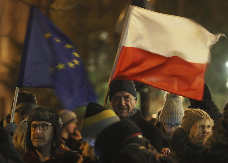 People holding a Poland and European Union flags take part in a protest outside Poland's parliament building as lawmakers voted to approve the much-criticized legislation that allows politicians to fire judges who criticize their decisions, in Warsaw, Poland, Thursday, Jan. 23, 2020. Poland's lawmakers gave their final approval Thursday to legislation that will allow politicians to fire judges who criticize their decisions, a change that European legal experts warn will undermine judicial independence. (AP Photo/Czarek Sokolowski)
