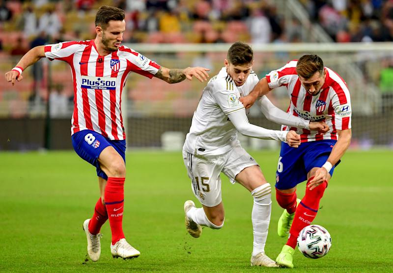Real Madrid's Uruguayan midfielder Federico Valverde (C) is marked by Atletico Madrid's Spanish midfielder Saul Niguez (L) and Atletico Madrid's Mexican midfielder Hector Herrera during the Spanish Super Cup final between Real Madrid and Atletico Madrid on January 12, 2020, at the King Abdullah Sports City in the Saudi Arabian port city of Jeddah. (Photo by Giuseppe CACACE / AFP) (Photo by GIUSEPPE CACACE/AFP via Getty Images)