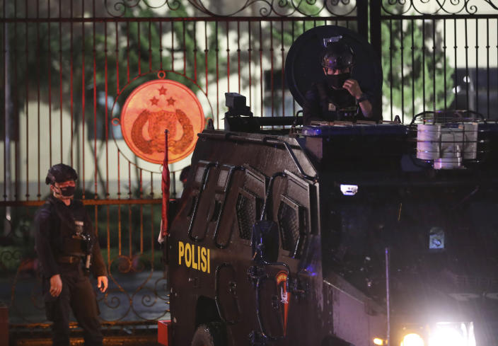 An officer mans his position at an armored vehicle parked at the National Police Headquarters following a suspected militant attack in Jakarta, Indonesia, Wednesday, March 31, 2021. A woman entered the Indonesian National Police Headquarters in Jakarta and pointed a gun at several officers before being shot dead by police, in the latest in a series of militant attacks in the world's most populous Muslim nation. (AP Photo/Dita Alangkara)