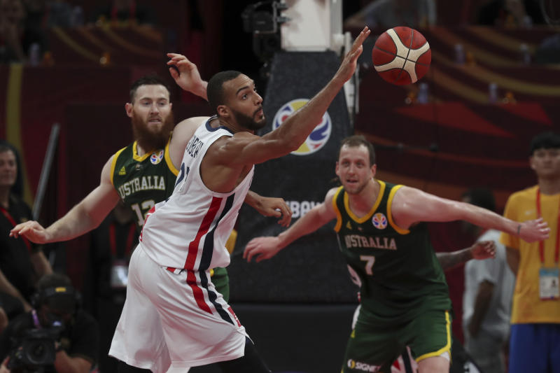Rudy Gobert of France reaches for the ball over Aron Baynes, left, and Joe Ingles, right, of Australia during their third placing match for the FIBA Basketball World Cup at the Cadillac Arena in Beijing, Saturday, Sept. 13, 2019. (AP Photo/Ng Han Guan)