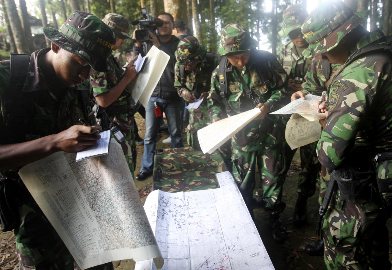 Indonesian soldiers read maps at Taman Nasional Halimun Salak in Sukabumi, West Java, Indonesia, Thursday morning, May 10, 2012. Search and rescue teams were scouring the slopes of a dormant volcano in western Indonesia early Thursday for signs of a new Russian-made passenger plane that dropped off the radar while on a demonstration flight Wednesday. (AP Photo/Achmad Ibrahim)