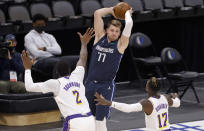 Dallas Mavericks guard Luka Doncic (77) looks to pass over Los Angeles Lakers center Andre Drummond (2) and guard Dennis Schroeder (17) during the first half of an NBA basketball game Saturday, April 24, 2021, in Dallas. (AP Photo/Ron Jenkins)