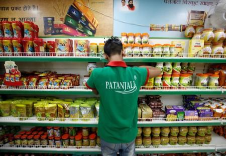 A worker arranges consumable goods inside a Patanjali store in Ahmedabad
